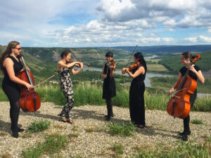 String quintet playing instruments outdoors